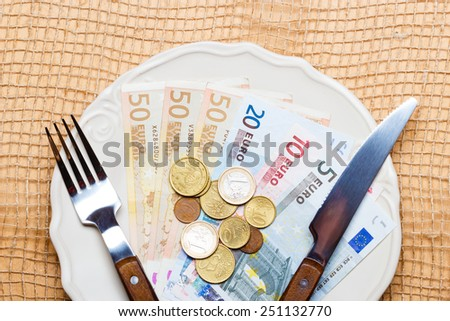 Cost of living, price of food and eating wealth concept. Euro money on kitchen table, plate with cutlery - stock photo