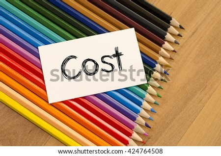 Cost text concept and colored pencil on wooden background