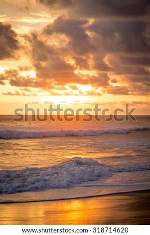 Costa Rica, Playa Carmen beach at sunset, with surfers and waves. Paceful outdoor scene - stock photo