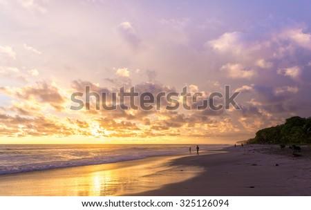 Costa Rica, Playa Santa Teresa at sunset, surfers and tourists on the beach - stock photo