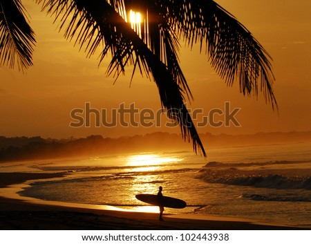 Costa Rica sunset with surfer admiring the waves - stock photo