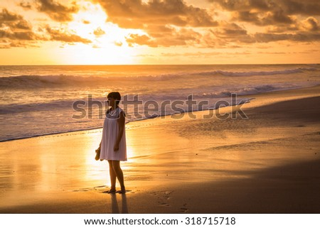 Costa Rica, young girl looking at the ocean at sunset, Playa Carmen.