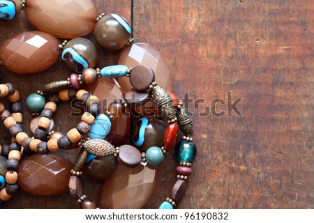 Costume Jewelry. Vintage female bracelets and necklace on wooden surface - stock photo