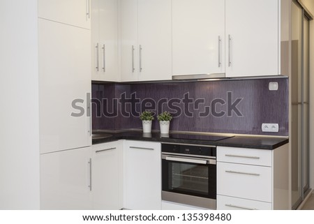 Cosy flat - kitchen with a purple wall - stock photo