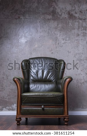 Cosy green leather armchair in front of the wall