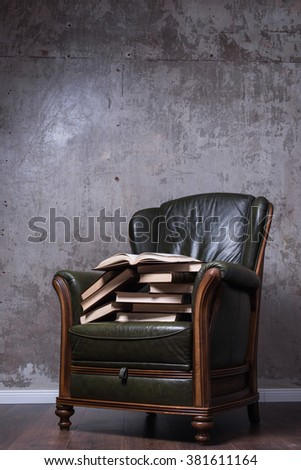 Cosy green leather armchair with books in front of the wall - stock photo
