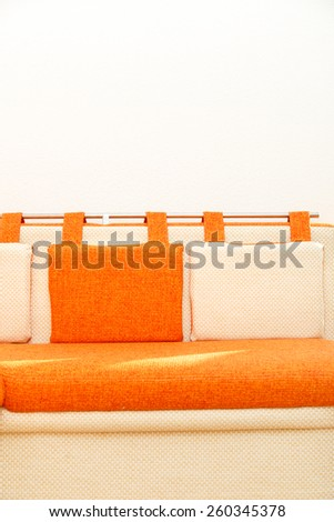 Cosy orange and white sofa with pillows - stock photo