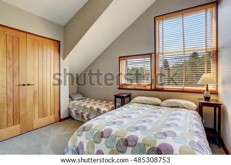 Cosy upstairs bedroom with minimal design and closet. Small kid's bed in the corner with matching colorful bedding .Northwest, USA
