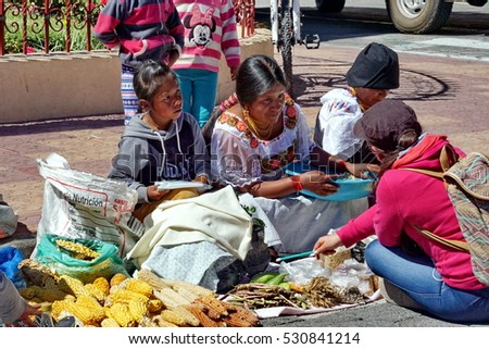COTACACHI, ECUADOR -  AUGUST 12, 2016: Women in traditional dress displaying fresh vegetables, at Muyu Raymi, the indigenous seed festival