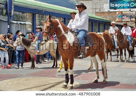 COTACACHI, ECUADOR - CIRCA JUNE 2015: Riders on brown horses on the main road passing through the village in the Paseo del Chagra, or horse parade