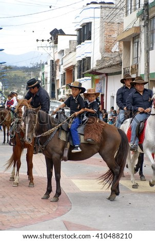 COTACACHI, ECUADOR - CIRCA MAY 2013: Boy rides with his younger brother behind him in the Paseo de Chagra horse parade