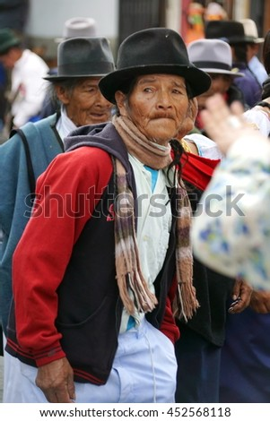 COTACACHI, ECUADOR - JUNE 23, 2016: Children parade on the first day of Inti Raymi, the Quechua solstice celebration.  An elderly man marches with a seniors group.