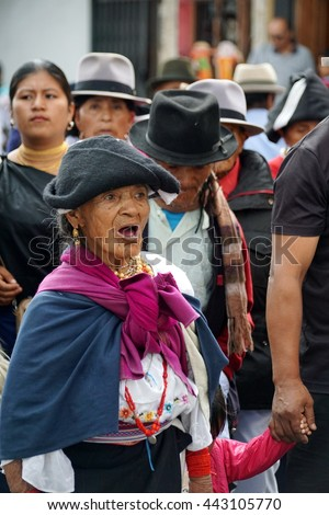 COTACACHI, ECUADOR - JUNE 23, 2016: Children's parade for Inti Raymi, the Quechua solstice celebration.  Elderly woman in traditional dress joins the procession with a senior group.
