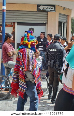 COTACACHI, ECUADOR - JUNE 23, 2016: Children's parade in Inti Raymi, the Quechua solstice celebration.  Man in a devil mask marches in the procession. - stock photo