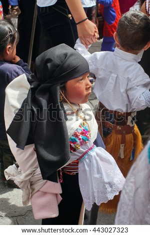 COTACACHI, ECUADOR - JUNE 23, 2016: Children's parade in Inti Raymi, the Quechua solstice celebration.  Young girl in traditional clothing marching with her mother.