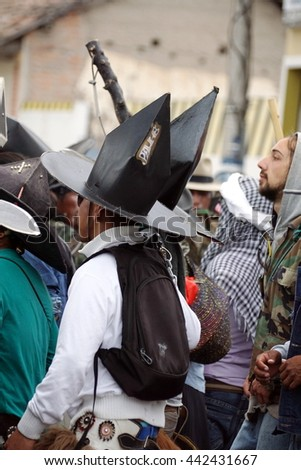 COTACACHI, ECUADOR - JUNE 24, 2016: Inti Raymi, the Quechua solstice celebration, with a history of violence in Cotacachi.  Men in costumes rush forward, and stomp around the square.