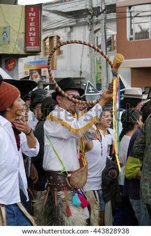 COTACACHI, ECUADOR - JUNE 25, 2016: Inti Raymi, the Quechua solstice celebration, with a history of violence in Cotacachi.  Man blows a horn during the parade - stock photo