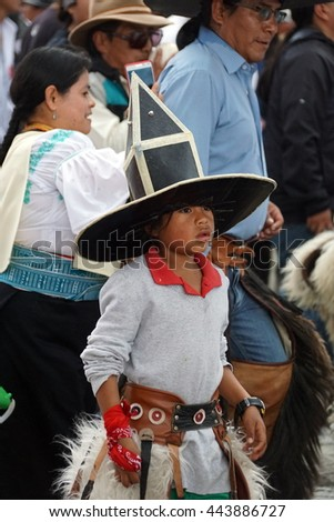 COTACACHI, ECUADOR - JUNE 25, 2016: Inti Raymi, the Quechua solstice celebration, with a history of violence in Cotacachi.  Children in costume dance and parade ahead of the men.