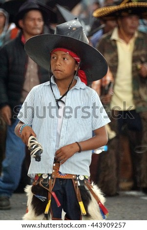 COTACACHI, ECUADOR - JUNE 25, 2016: Inti Raymi, the Quechua solstice celebration, with a history of violence in Cotacachi.  Boy parades ahead of the group of men.