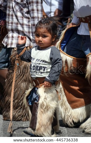 COTACACHI, ECUADOR - JUNE 29, 2016: Inti Raymi, the Quechua solstice celebration, with a history of violence in Cotacachi. Young child parades with his father.