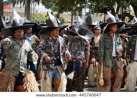 "COTACACHI, ECUADOR - JUNE 29, 2016: Inti Raymi, the Quechua solstice celebration, with a history of violence in Cotacachi. Men march forward to ""take the square."""
