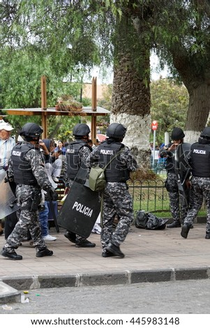 COTACACHI, ECUADOR - JUNE 29, 2016: Inti Raymi, the Quechua solstice celebration, with a history of violence in Cotacachi.  Riot police are staged in the park in case of violence.