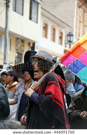 COTACACHI, ECUADOR - JUNE 29, 2016: Inti Raymi, the Quechua solstice celebration, with a history of violence in Cotacachi.  Men stomp and dance to awaken Mother Earth under the Quechua rainbow flag.