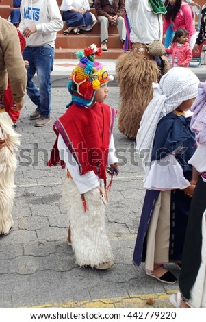 COTACACHI, ECUADOR - JUNE 23, 2016: Inti Raymi, the Quechua solstice festival, children's parade.  Boy dances in a circle wearing a red poncho and a devil mask. - stock photo
