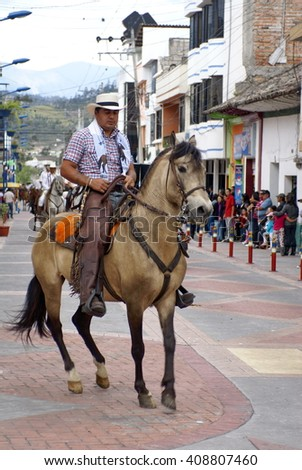 COTACACHI, ECUADOR - MAY 19, 2013: Man on a tan horse, preparing it to do a trick, in the Paseo de Chagra, or horse parade