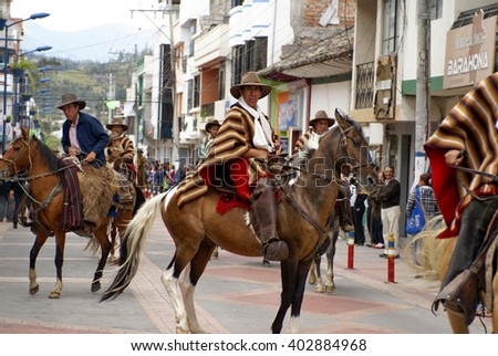 COTACACHI, ECUADOR - MAY 19, 2013: Men in a ponchos ride horses down the main street of the town, and do tricks, in the Paseo do Chagra - stock photo