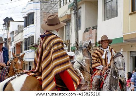 COTACACHI, ECUADOR - MAY 19, 2013: Men in brown ponchos on horses in the Paseo de Chagra, or Horse Parade - stock photo