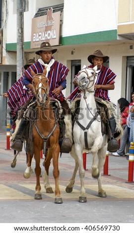COTACACHI, ECUADOR - MAY 19, 2013: Men in ponchos in the Paseo de Chagras horse parade - stock photo