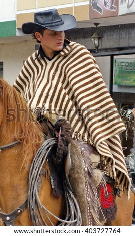 COTACACHI, ECUADOR - MAY 19, 2013: Young woman in a poncho, on a horse in the Paseo de Chagra parade - stock photo