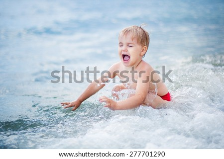 Cote happy blond boy playing at shallow water wave - stock photo