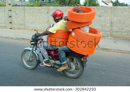 Cotonou, Benin: May 26: A man and a motorcycle taxi operator ride carrying several rolls of garden hose on May 26, 2015 in Cotonou, Benin. - stock photo