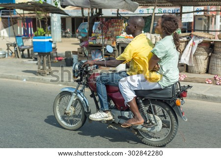 Cotonou, Benin: May 26: A woman rides a hired Motorcycle taxi, the most common means of hired transportation in the city, on May 26, 2015 in Cotonou, Benin. - stock photo
