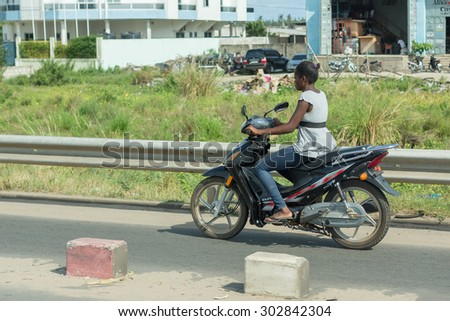 Cotonou, Benin: May 26: A woman rides a Motorcycle, the most common means of  transportation in the city, on May 26, 2015 in Cotonou, Benin. - stock photo