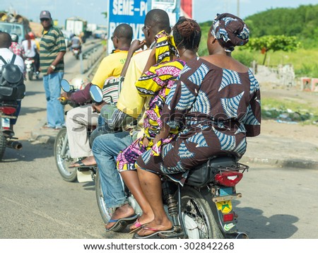 Cotonou, Benin: May 26:  People hire motorcycle taxis to move around in the city of Benin, one of the most common means of hired transportation in the city, on May 26, 2015 in Cotonou, Benin. - stock photo