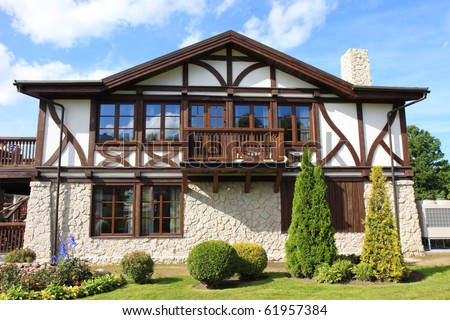 Cottage and small garden on a blue sky background - stock photo