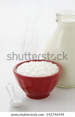 Cottage cheese and fresh milk on vintage french table linen. - stock photo