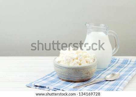 Cottage cheese and milk on white wooden table - stock photo