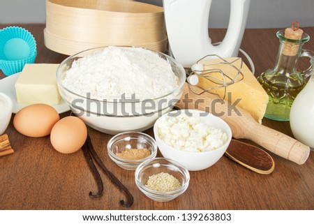 Cottage cheese, cheese,spices, butter, mixer and cake pan on a table