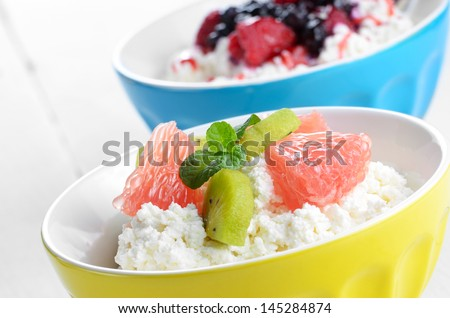 Cottage cheese in bowl with kiwi grapefruit and mint - stock photo