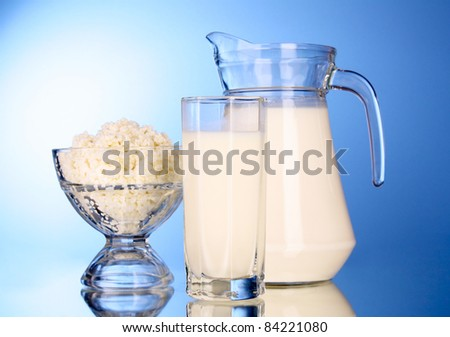 Cottage cheese  in bowl with milk on blue background