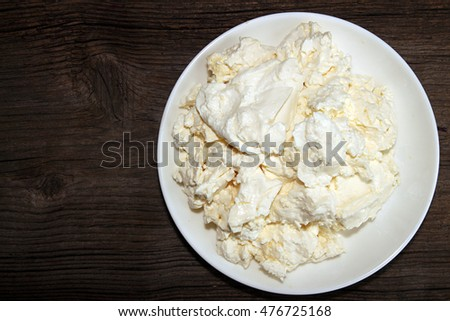 Cottage cheese in white plate on old wooden table.