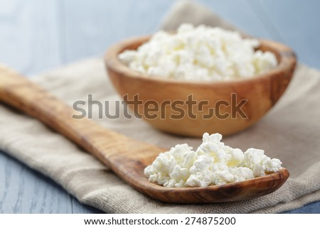 cottage cheese in wood bowl on blue wooden table - stock photo
