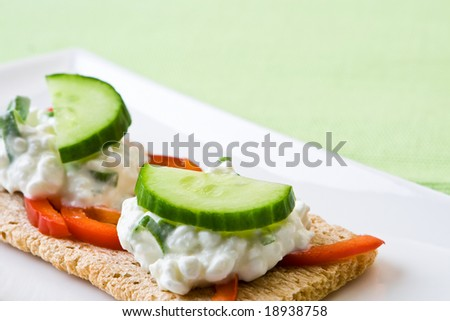 Cottage cheese on crispbread with tomato with cucumber - stock photo