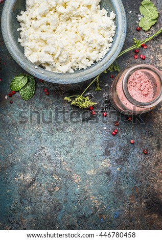 Cottage cheese or Feta cheese in blue bowl with fresh seasoning and salt on dark rustic background, top view, border - stock photo