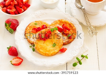 cottage cheese pancakes (cheese cakes) with strawberries and cream.