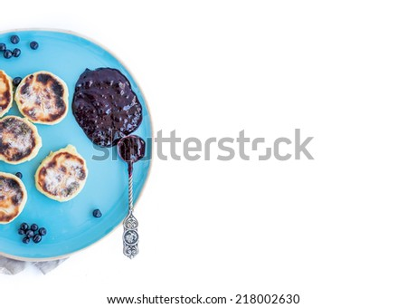 Cottage cheese pancakes with fresh blackberries and black-currant jam on a blue ceramic plate with a silver tea-spoon on a white background - stock photo
